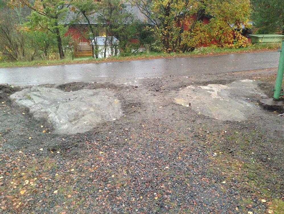 Berg sticker upp ur grusad parkering innan stenspräckning